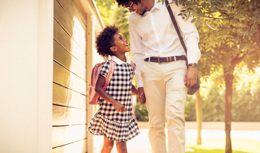 What's new in school? African American father and his daughter walking trough city park.